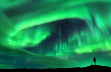 Aurora borealis and silhouette of standing man. Lofoten islands,