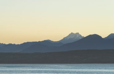 Couple kayaking in the Hood canal with Olympic National Park in