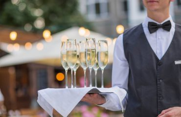 Catering service waiter holding a tray with glasses of Italian and French wine prosecco and champagne for tasting